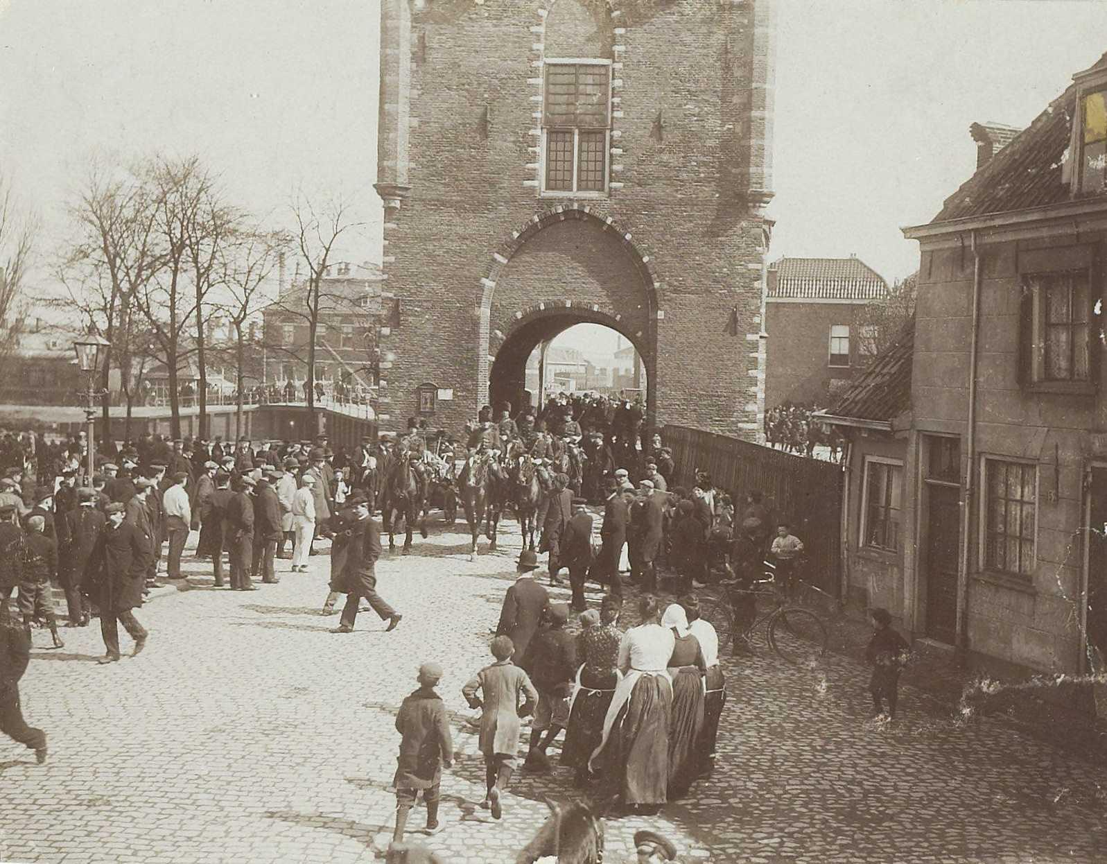 Foto van werkwilligen die onder bescherming van een aantal Huzaren de HIJSM-werkplaatsen verlaten tijdens de spoorwegstaking van 1903.
